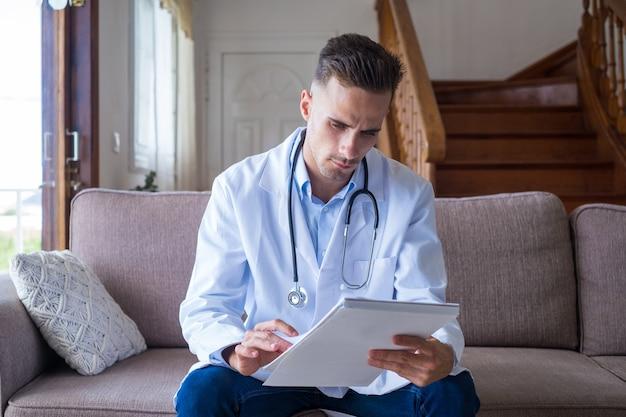 Skupiony młody lekarz mężczyzna w sofie i fartuchu medycznym pracuje z papierową książką metrykalną, robi notatki, zarządza wizytami pacjentów, rejestruje leczenie, siedzi na kanapie w domu.