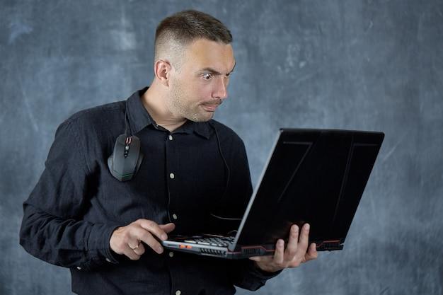 Skupiony młody mężczyzna pozuje na tle tablicy z laptopem w dłoniach