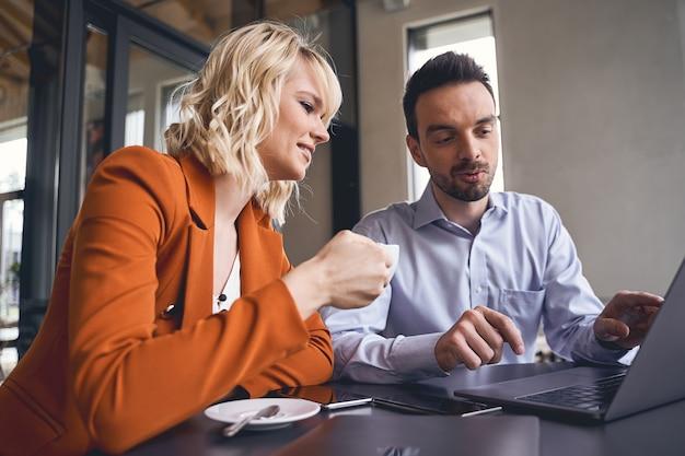Skupiony młody mężczyzna wskazujący coś na ekranie laptopa w kierunku swojej stylowej blond szefowej