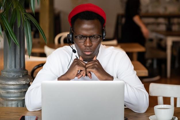 Skupiony murzyn w słuchawkach ogląda seminarium edukacyjne na laptopie, zdalnie pracuje online w kawiarni