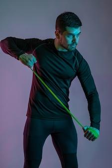 Skupiony, muskularny mężczyzna ćwiczący z pętlą oporową