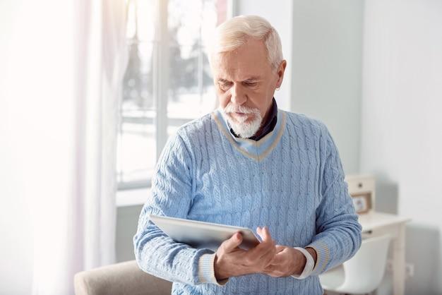 Skupiony na czytaniu. piękny starszy brodacz trzymający tablet i czytający z niego, całkowicie zanurzony w książce