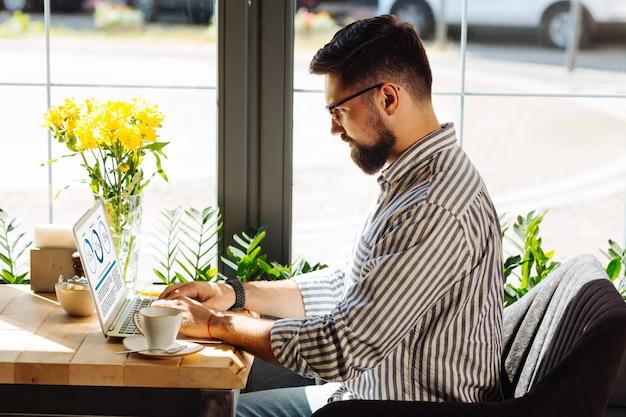 Skupiony na pracy. przystojny poważny mężczyzna piszący tekst podczas pracy na laptopie