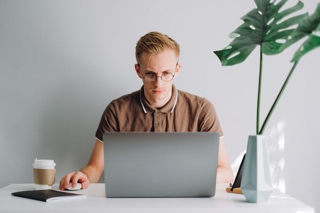 Skupiony programista programista mobilny człowiek pisze kod programu na laptopie w biurze domowym