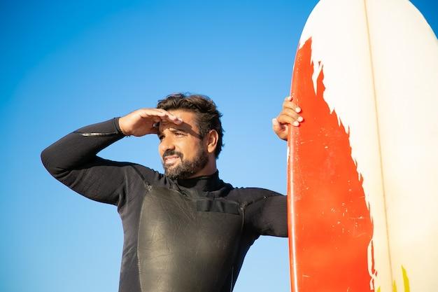 Skupiony przystojny surfer wpatrując się w dal