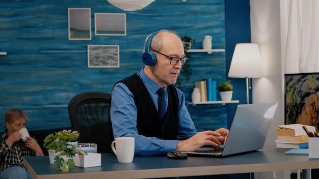 Skupiony stary przedsiębiorca ze słuchawkami słuchający muzyki i sprawdzający grafikę piszącą na laptopie pracującym w domu