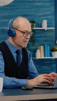 Skupiony stary przedsiębiorca ze słuchawkami słuchający muzyki piszącej na laptopie