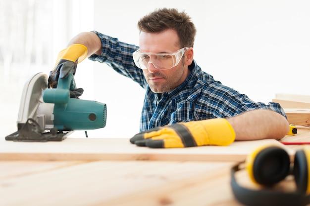 Skupiony stolarz wycinający drewniane deski