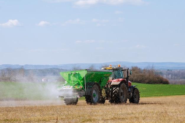 Skutc, czechy - 23 marca 2020 r.: ciągnik rozsiewający nawóz na polu trawiastym. prace rolnicze.
