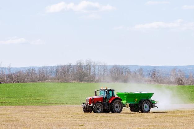 Skutc, czechy - 23 marca 2020: traktor rozsiewający nawóz na polu trawiastym. praca rolnicza.