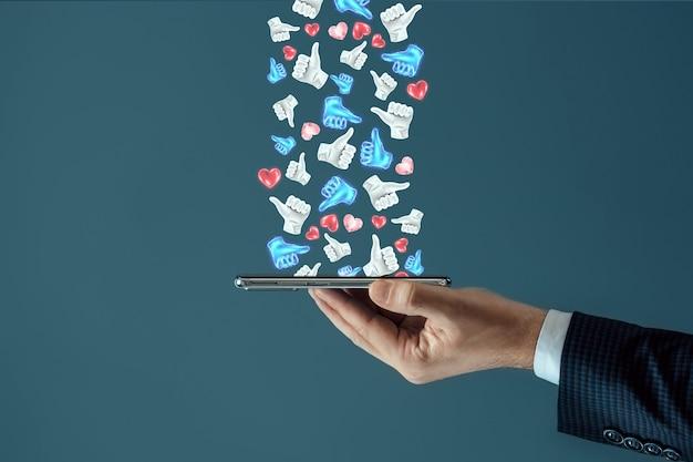 Skuteczna strategia reklamowa w mediach społecznościowych. sporo lajków spada na smartfona. pojęcie marketingu kreatywnego, popularność, wielu subskrybentów.
