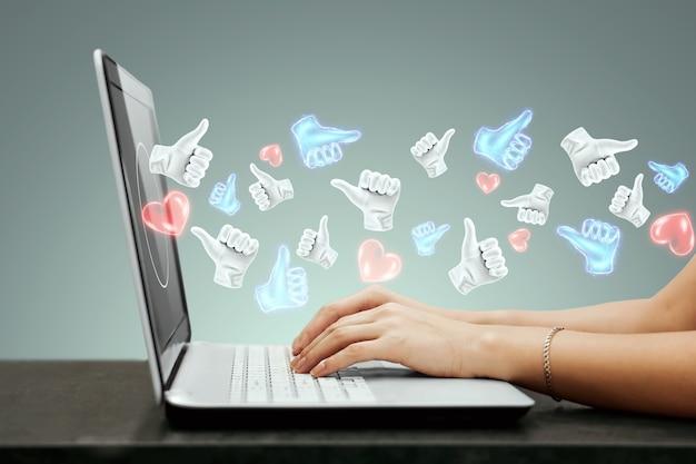 Skuteczna strategia reklamowa w mediach społecznościowych. wiele lajków wylatuje z laptopa. pojęcie marketingu kreatywnego, popularność, wielu subskrybentów.