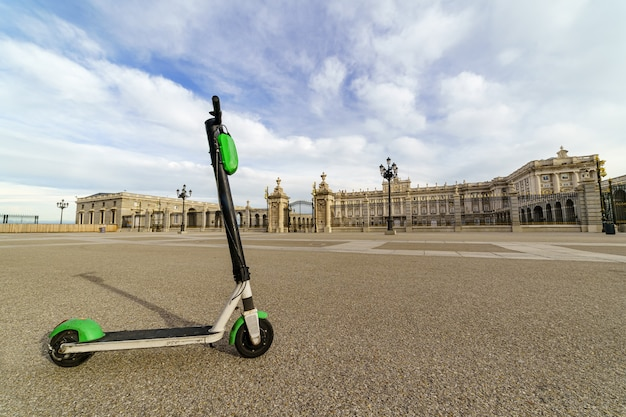 Skuter elektryczny na esplanadzie pałacu królewskiego w madrycie w słoneczny dzień. hiszpania.