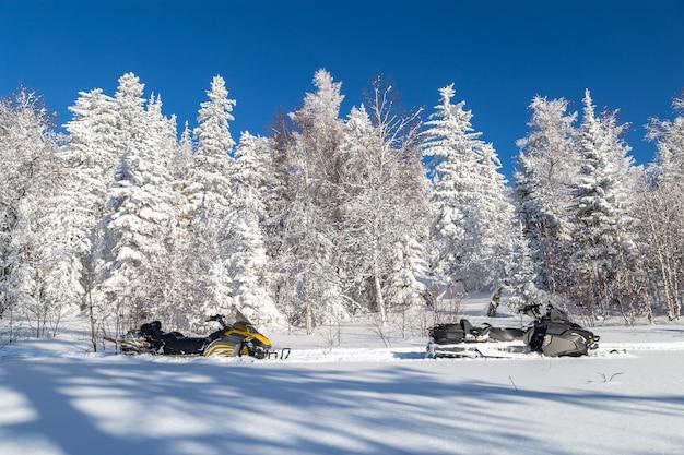 Skutery śnieżne w lesie zimą.