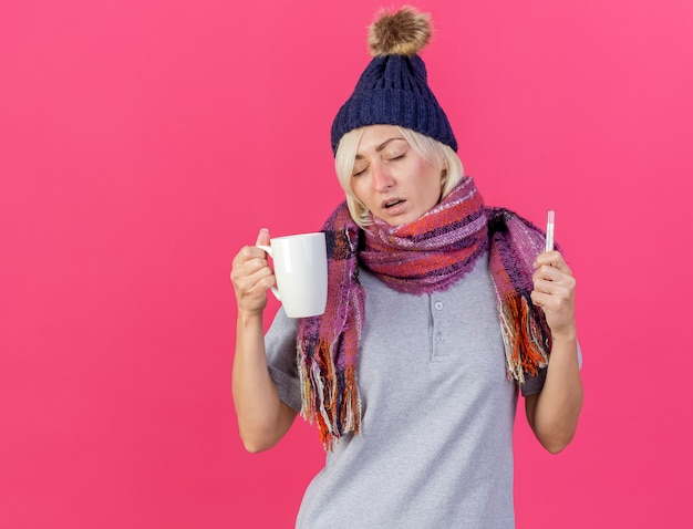 Słaba młoda blondynka chora słowiańska chora czapka zimowa i szalik trzyma kubek
