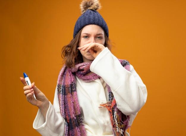 Słaba młoda chora dziewczyna ubrana w białą szatę i czapkę zimową z szalikiem trzyma termometr wycierając nos ręką odizolowaną na pomarańczowo