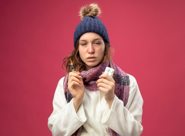 Słaba młoda chora dziewczyna ubrana w białą szatę i czapkę zimową z szalikiem, trzymając strzykawkę z pigułkami na różowym tle