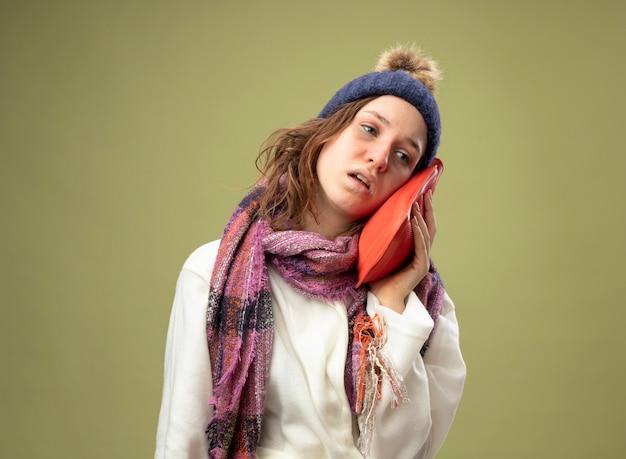 Słaba młoda chora dziewczyna ubrana w białą szatę i czapkę zimową z szalikiem zakładająca na policzek torbę z gorącą wodą, odizolowaną na oliwkowej zieleni