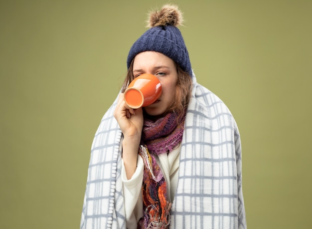 Słaba młoda chora dziewczyna ubrana w białą szatę i czapkę zimową z szalikiem zawiniętym w kratę pije herbatę na oliwkowym zielonym tle