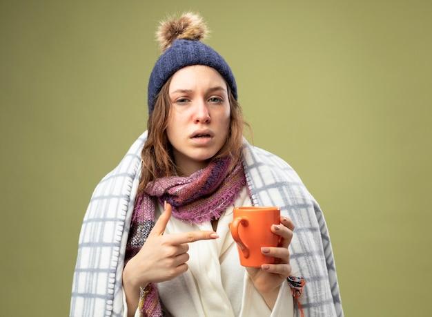 Słaba młoda chora dziewczyna w białej szacie i czapce zimowej z szalikiem owiniętym w kratę i wskazuje na filiżankę herbaty odizolowaną na oliwkowej zieleni