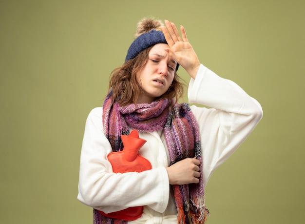 Słaba młoda chora dziewczyna w białej szacie i czapce zimowej z szalikiem trzymająca torbę z gorącą wodą kładąca dłoń na czole odizolowana na oliwkowej zieleni