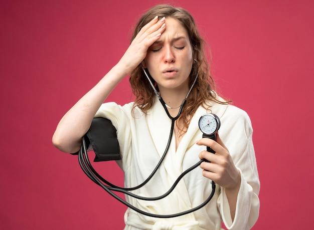 Słaba młoda chora dziewczyna z zamkniętymi oczami w białej szacie mierzącej własne ciśnienie za pomocą ciśnieniomierza kładącego dłoń na czole odizolowanym na różowo