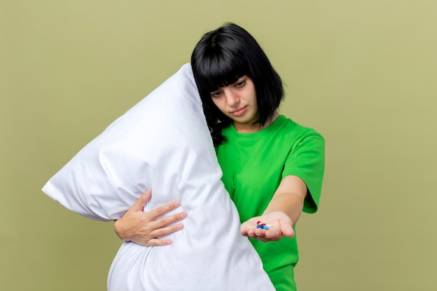 Słaba młoda chora dziewczynka kaukaska trzymająca poduszkę wyciągająca kapsułki medyczne w kierunku patrzenia na rękę na tle oliwkowej ściany z miejsca na kopię