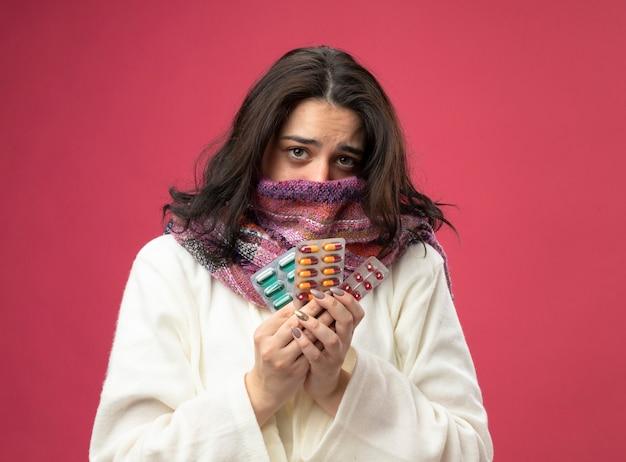 Słaba młoda chora kobieta ubrana w szlafrok i szalik zakrywający usta szalikiem, patrząc z przodu, trzymając paczki pigułek medycznych odizolowane na różowej ścianie