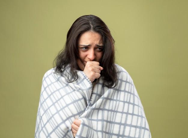 Słaba młoda kaukaska chora dziewczyna ubrana w szatę owiniętą w kratę patrząc w bok, kaszląc, trzymając pięść w pobliżu ust, chwytając kratę na tle oliwkowej zieleni z miejscem na kopię