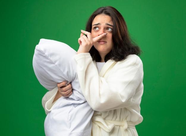 Słaba młoda kaukaska chora dziewczyna ubrana w szatę stojącą w widoku profilu przytulająca poduszkę patrząc w bok wycierając nos na białym tle na zielonym tle z miejscem na kopię