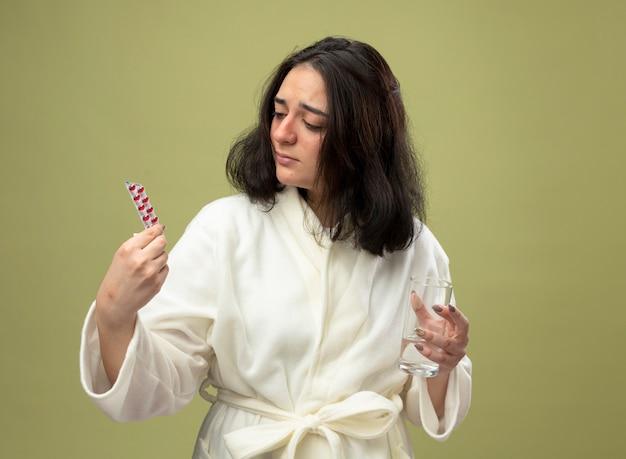 Słaba młoda kaukaska chora dziewczyna ubrana w szatę z paczką medycznych pigułek szklanka wody patrząc na pigułki odizolowane na oliwkowym tle z miejsca na kopię