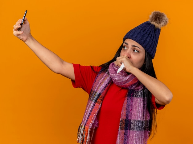 Słaba młoda kaukaska chora dziewczyna w czapce zimowej i szaliku przy selfie, kaszel trzymając pięść na ustach z serwetką w dłoni na białym tle na pomarańczowym tle