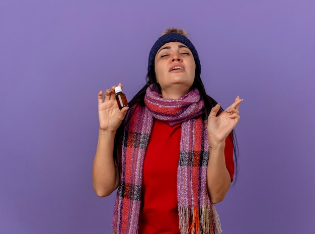 Słaba młoda kaukaska chora dziewczyna w czapce zimowej i szaliku trzymająca lekarstwo w szkle robi gest powodzenia z zamkniętymi oczami na białym tle na fioletowym tle z miejsca na kopię