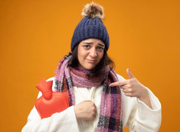 Słaba młoda kaukaski chora dziewczyna ubrana w płaszcz zimowy kapelusz i szalik trzyma i wskazuje na worek z gorącą wodą na pomarańczowej ścianie