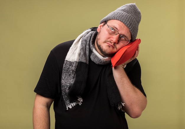 Słaba, pochylona głowa, patrząca w górę, chory mężczyzna w średnim wieku, ubrany w zimową czapkę i szalik, zakładając worek z gorącą wodą na policzek