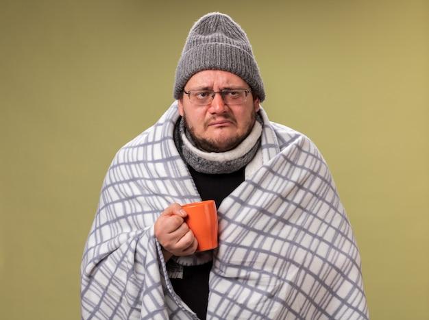 Słabo wyglądający, chory mężczyzna w średnim wieku, ubrany w zimową czapkę i szalik owinięty w kratę, trzymający filiżankę herbaty