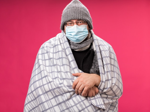 Słaby, chory mężczyzna w średnim wieku, noszący czapkę zimową z szalikiem i maską medyczną owinięty w kratę odizolowaną na różowej ścianie