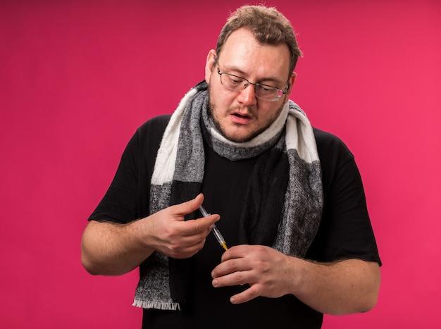 Słaby, chory mężczyzna w średnim wieku, ubrany w szalik trzymający strzykawkę z ampułką