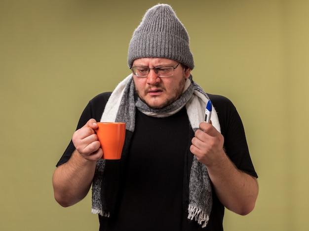 Słaby, chory mężczyzna w średnim wieku, ubrany w zimową czapkę i szalik, trzymający filiżankę herbaty z termometrem