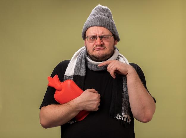 Słaby, chory mężczyzna w średnim wieku, ubrany w zimową czapkę i szalik, trzymający i wskazujący na torbę z gorącą wodą odizolowaną na oliwkowozielonej ścianie