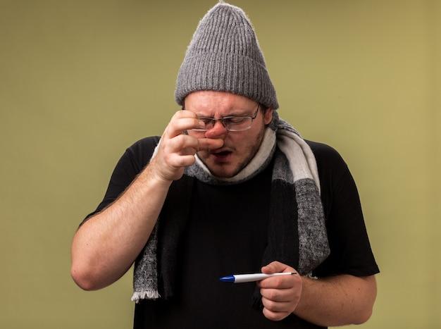 Słaby, chory mężczyzna w średnim wieku, ubrany w zimową czapkę i szalik, trzymający termometr, wycierający nos serwetką