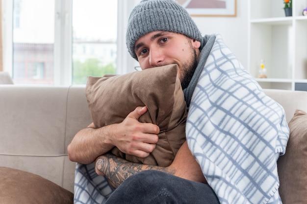 Słaby młody chory mężczyzna ubrany w szalik i czapkę zimową, siedzący na kanapie w salonie, owinięty w koc, przytulający się do poduszki patrząc w kamerę