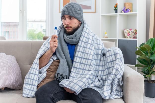 Słaby młody chory mężczyzna ubrany w szalik i czapkę zimową zawiniętą w koc, siedzący na kanapie w salonie, trzymający termometr patrząc w bok