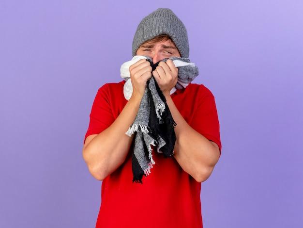 Słaby młody przystojny blondyn chory w czapce zimowej i szaliku patrząc na aparat zakrywający usta szalikiem patrząc na aparat odizolowany na fioletowym tle z miejsca na kopię