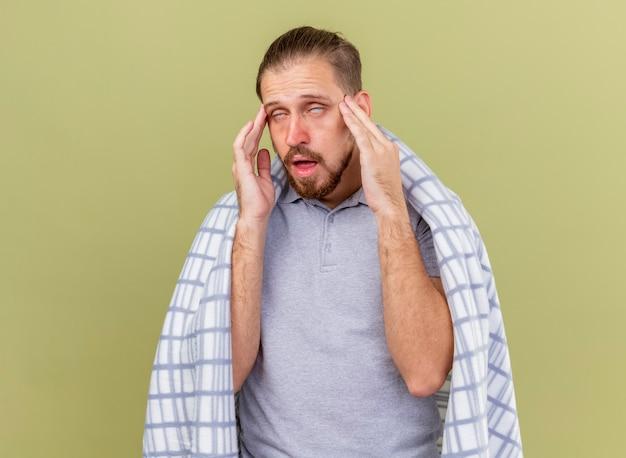 Słaby młody przystojny słowiański chory mężczyzna owinięty w kratę przewracającymi oczami, trzymając ręce na skroniach odizolowanych na oliwkowej ścianie z miejscem na kopię