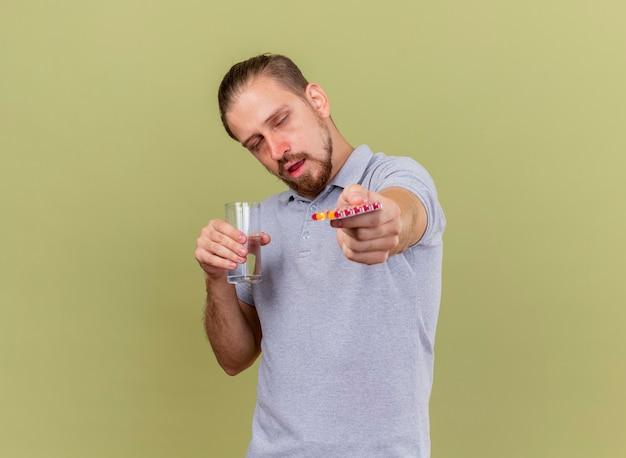 Słaby młody przystojny słowiański chory mężczyzna trzyma paczkę kapsułek i szklankę wody wyciągając paczkę kapsułek w kierunku aparatu z zamkniętymi oczami odizolowanymi na oliwkowozielonym tle z miejscem na kopię