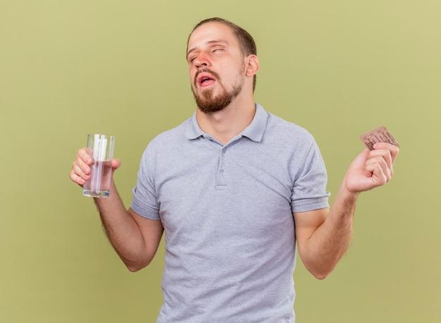 Słaby młody przystojny słowiański chory mężczyzna trzyma paczkę kapsułek i szklankę wody z zamkniętymi oczami na białym tle na oliwkowej ścianie