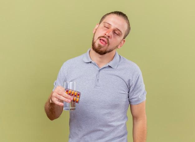 Słaby młody przystojny słowiański chory mężczyzna trzymający paczkę kapsułek i szklankę wody z zamkniętymi oczami odizolowanymi na oliwkowej ścianie z miejscem na kopię