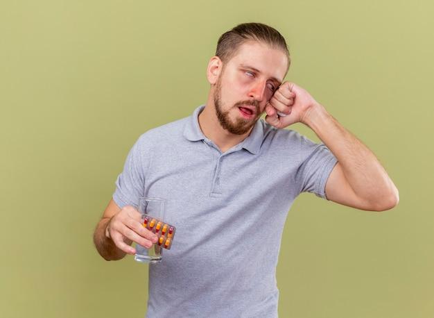 Słaby młody przystojny słowiański chory mężczyzna trzymający paczkę kapsułek szklanka wody i serwetka dotykająca twarzy przewracających oczami odizolowana na oliwkowej ścianie z przestrzenią do kopiowania