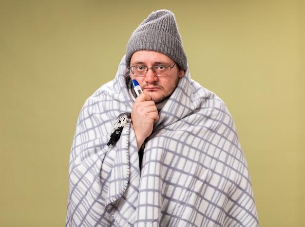 Słaby, patrzący na kamerę, chory mężczyzna w średnim wieku, ubrany w zimową czapkę i szalik owinięty w kratę trzymającą termometr